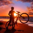 Woman with bicycle on the beach - Stock Photo