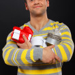 Stock Photo: Young man is ready for celebration and holding gifts