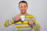 Man is holding a mug and demonstrating that he likes his drink — Stock Photo