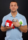 Self confident young man with a bunch of gifts — Stock Photo