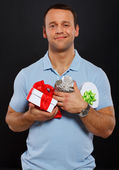 Flirting guy is holding a bunch of presents — Foto de Stock