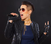 Singing woman is demonstrating rockers gesture — Stock Photo