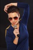 Atrakcyjna kobieta w niebieska sukienka śpiewa na aparat — Zdjęcie stockowe