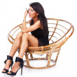 Royalty-Free Stock Photo: Sexy brunette in black dress  is sitting on chair