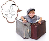 Young boy is playing with suitcases and thinking about boat — Stock Photo