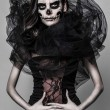 Постер, плакат: Brunette with a greasepaint of a skull in the dark atmosphere