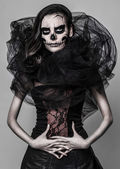 Brunette with a greasepaint of a skull in the dark atmosphere — Foto Stock