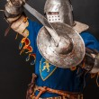 Stock Photo: Knight is demonstrating his shield and sword