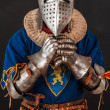 Stock Photo: Knight in armor is praying