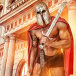 Постер, плакат: Powerfull warrior in red mantle and helmet near the building wit