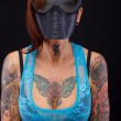 Redhead woman with tattooed body in big black mask — Stock Photo