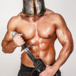 Nude barbarian in helmet and with sword — Stock Photo