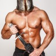 Nude barbarian in helmet and with sword — Stock Photo #23005004