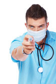 Young doctor with a stylish haircut is pointing with a syringe — Stock Photo