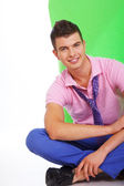 Charming guy with a pretty smile sitting on the floor — Stock Photo