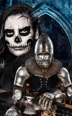 Dark skulled face woman and iron knight — Stock Photo