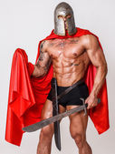Shirtless warrior in pants and mantle with a grin on his face — Stock Photo