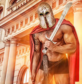 Powerfull warrior in red mantle and helmet near the building wit — Stock Photo