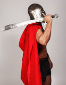 Sideview of shirtless warrior who is holding his sword — Stock Photo