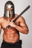 Shirtless warrior in helmet and with sword — Stock Photo