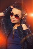 Beautiful woman in sunglasses with orange lights — Stock Photo