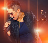 Hot rocker is singing in microphone — Stock Photo