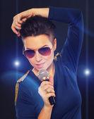 Stylish singing girl with blue lights — Stock Photo