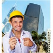 Smiling man in yellow hardhat with a key in his hands — Stock Photo