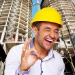 Man in yellow hardhat in front of buildings construction — Stock Photo