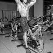 Shirtless sportsman is having workout on bicycle in gym — Stock Photo