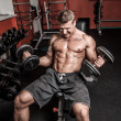 Stock Photo: Shirtless bodybuilder is having really hard workout