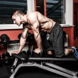 图库照片: Bodybuildres is doing exercises to build better triceps