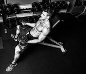 Topless bodybuilder is lifting heavy weights — Stock Photo