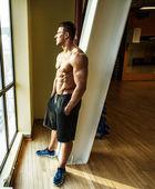 上半身裸のスポーツマンはウィンドウを見ながら休憩します。 — ストック写真