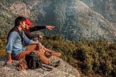 Two friends are sitting on the mountain and one of them is point — Stock Photo