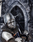 Armed knight on a ancient building background — Stock Photo