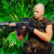 Bold soldier with weapon in jungles - Stock Photo