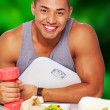 Handsome healthy man with food, scales and dumbbells — Stock Photo
