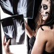 Skull faced girl with x-ray pictures — Stock Photo