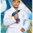 Hot worker in uniform is holding a drill — Stock Photo