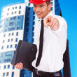 Young happy businessman is pointing with his finger - Stock Photo
