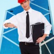 Young nice guy in hardhat with a folders — Stock Photo #23869485