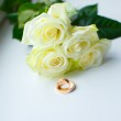 White roses and golden rings — Stock Photo