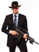 Man in suit and hat with weapon in hands — Stock Photo