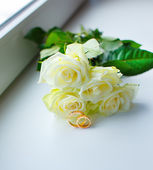 Bouquet of white roses and wedding rings — Stock Photo