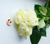 Golden rings and white roses — Stock Photo