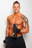 Attractive fit man with a dumbbells — Stock Photo