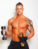 Sexy guy with well looking body is holding dumbbells — Stock Photo