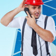 Confused worker is talking on the phone outdoors — Stock Photo #24457773