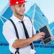 Smiling businessman in red hardhat is fooling around with a keyb — Stock Photo